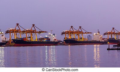 Big crane bridge shipping container cargo in shipyard at twilight. Logistic Import Export background.