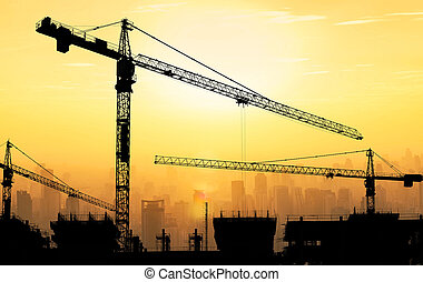 Big cranes and building construction against beautiful dusky sunset sky with cityscape in background.
