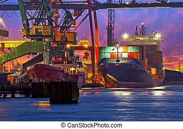 The unloading of a container ship at a large harbor terminal.