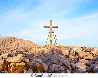 Big cross on top of mountain as typical in the Alps. Wooden cross with Buddhist praying flags