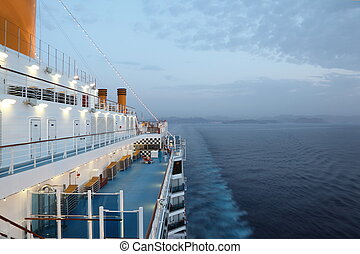big cruise ship riding in evening. light on. few of people on deck.