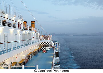 big cruise ship riding in evening. light on. few of people on deck of cruise ship