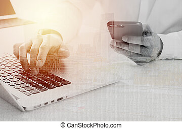 Big data analytics with business intelligence (BI) concept. businessman using mobile phone and laptop computer on white desk with building exposure