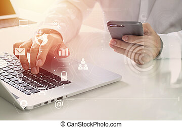 Big data analytics with business intelligence (BI) concept. businessman using mobile phone and laptop computer on white desk with VR chart and graph with icon