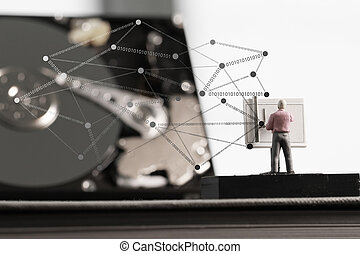 Big data concept-miniature engineer working with drafting table with open hard disk background