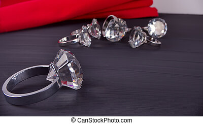 Big diamond ring on the table. In the background a bunch of rings and red table napkin
