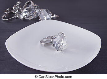 Big diamond ring on the white plate. In the background a bunch of big rings.