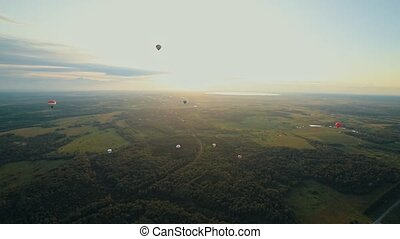 Big different air balloons flying above the green field and...