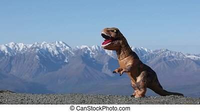 Beautiful installation outdoors on nature with prehistoric animal. Big dinosaur doll Tyrannosaurus Rex with person inside is dancing in mountains in amazing nature park. Inflatable doll.