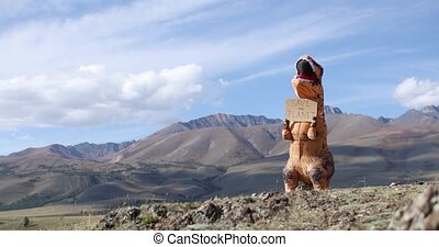 Big dinosaur doll with person inside is holding banner save ...