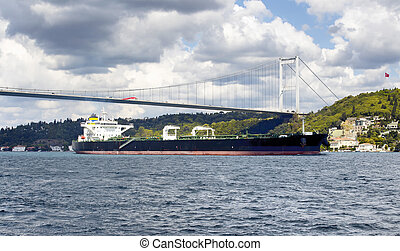Big, dry cargo ship / vessel crosses Bosphorus strait in Istanbul. Asian side and FSM (Fatih Sultan Mehmet) bridge are in the background. It is significant waterway located in northwestern Turkey