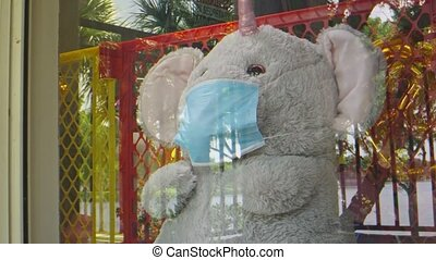 Slow motion moving away from an elephant stuffed animal wearing a face mask while sitting by a window