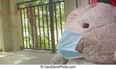 Slow motion of elephant stuffed animal wearing a face mask while sitting by a window