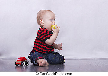 Big-eyed cute baby boy eating an apple
