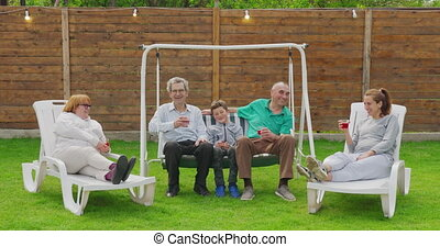 Big Family Garden Party Celebration. People are Drinking, Passing Dishes, Joking and Having Fun.