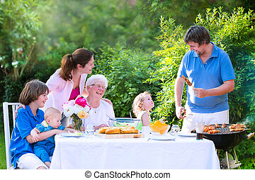 Big family grilling meat for lunch
