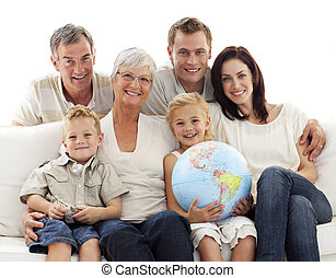 Big family on sofa holding a terrestrial globe - Happy big ...