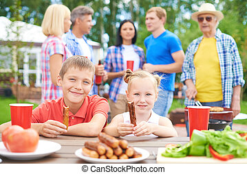 Big family on vacations - Children eating sausages during...