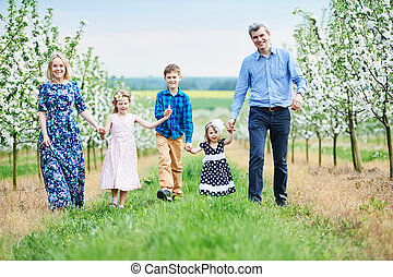 Big family outdoors. Three children and parents in spring blooming garden