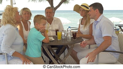 Big family sitting at table on the sea coast in city of Perea, Greece
