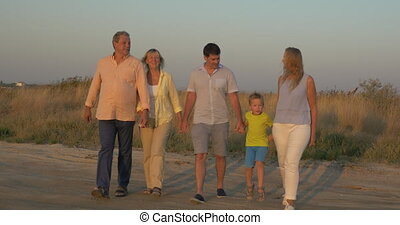 Big family walking in the countryside at sunset