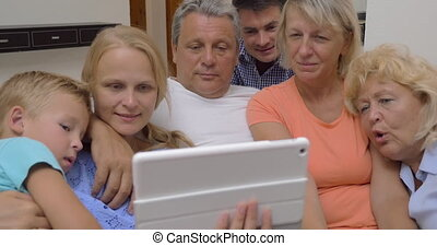 Big family watching video on digital tablet