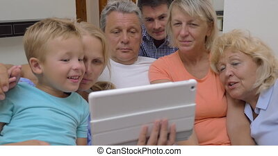 Big family with child watching tablet computer