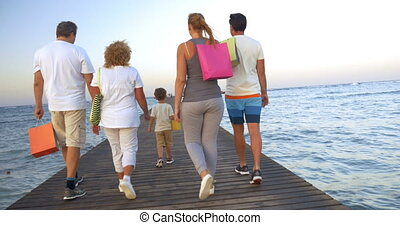 Big family with shopping bags on pier in the sea