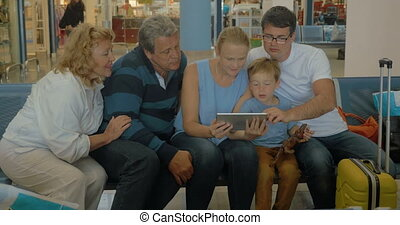 Big Family with Tablet in Waiting Room - Members of a big...