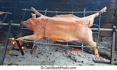 fat pig cooked on a spit in one piece during a village festival