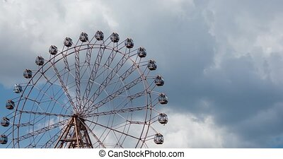 Big ferris wheel on blue sky and white clouds background, timelapse video.