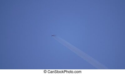 Big four engine commercial airplane leaving contrail in blue...