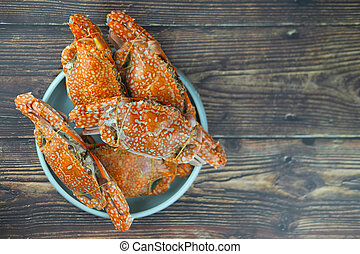 Big fresh steamed crab in plate on wood table.