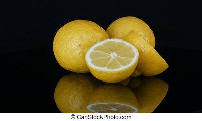 Big fresh yellow lemons on black mirror surface on a black...