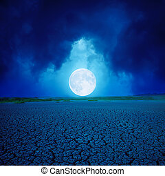 big full moon in clouds over desert