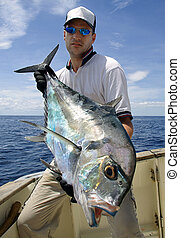 big game fishing - Happy fisherman holding a trevally jack