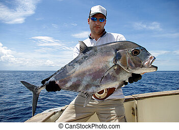 trevally jack - big game fishing - Happy fisherman holding a...