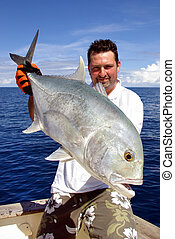 big game fishing. Happy fisherman holding a trevally jack