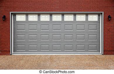 Big garage with gray doors, brick wall and asphalt driveway