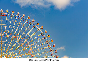Big giant wheel against blue sky in amusement park