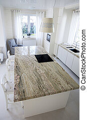Big granitic worktop in bright kitchen, vertical