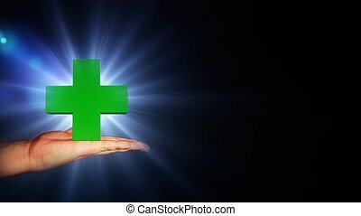 Big green cross with bright light in hand. 56. - Big green...