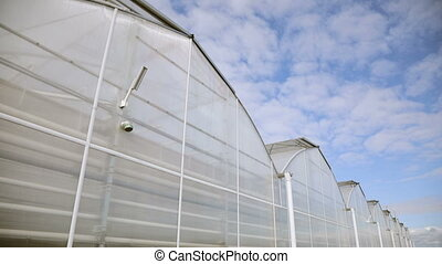 Big greenhouse with glass walls, foundations, gable roof,...