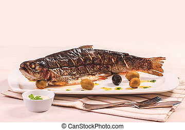 Big grilled trout with olive on plate