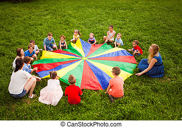 Big group of children playing parachute game