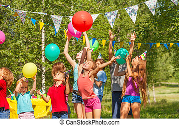 Big group of happy kids playing balloons outdoor