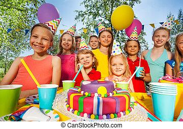 Big group of happy kids standing around B-day cake