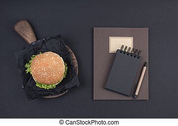 Big hamburger with sesame seeds on a black background. Fast food and free space for text. Notebook for school and office records, day planning. View from above.