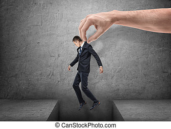 Big hand is bringing a businessman over a gap in the floor on gray background