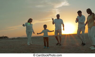 Big happy family dancing on the beach at sunset